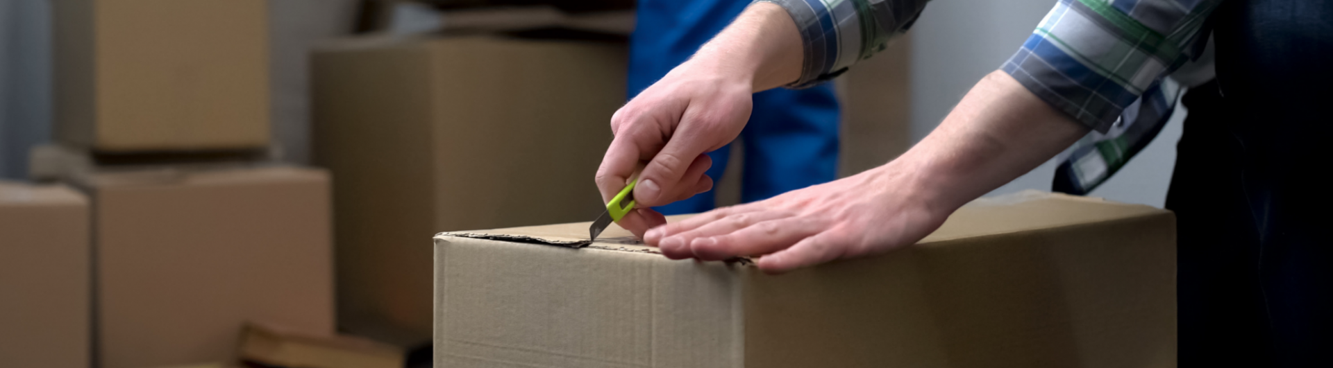 a packer from an international moving company uses a penknife to open a box